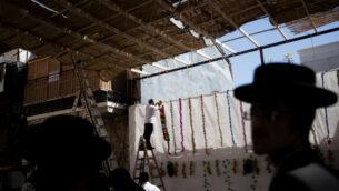 رجال يعلقون الزخارف في عرشية مبنية حديثا في حي مئة شعاريم الحريدي في القدس، 2 أكتوبر 2020 (Nati Shohat / Flash90)