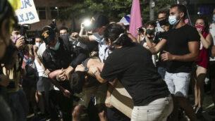 ضباط الشرطة يسحبون متظاهرا خلال احتجاجات ضد رئيس الوزراء بنيامين نتنياهو في ساحة 'هابيما' في تل أبيب، 3 أكتوبر 2020 (Miriam Alster / Flash90)