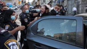 اشتباك بين عناصر من الشرطة ومتظاهرين حريديم خلال مظاهرة ضد تطبيق القيود المفروضة بسبب جائحة كورونا في حي مئة شعاريم بالقدس، 4 أكتوبر، 2020. (Nati Shohat/Flash90)
