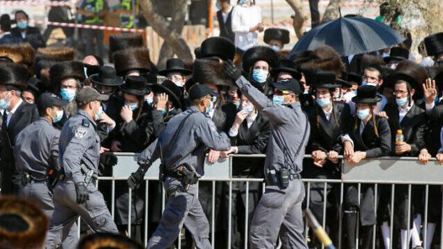 عناصر الشرطة ويهود متشددون خلال جنازة حاخام بيتسبرغ مردخاي لايفر في مدينة أشدود، 5 أكتوبر 2020 (Flash90)
