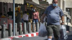 اشخاص يرتدون أقنعة الوجه في سوق محانيه يهودا في القدس، 5 أكتوبر 2020، خلال إغلاق على مستوى البلاد لمنع انتشار كوفيد-19. (Olivier Fitoussi / Flash90)