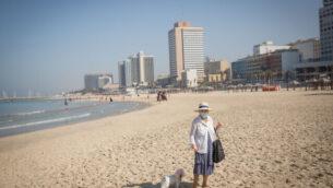 أشخاص على الشاطئ في تل أبيب، خلال إغلاق كامل على مستوى البلاد، 7 أكتوبر، 2020. (Miriam Alster / FLASH90)