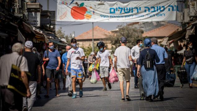 أشخاص يرتدون أقنعة الوجه يتسوقون في سوق محانيه يهودا في القدس، خلال إغلاق في جميع أنحاء البلاد لمنع انتشار كوفيد-19، 7 أكتوبر 2020 (Yonatan Sindel / Flash90)