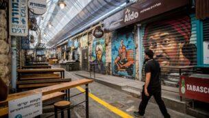 أشخاص يرتدون أقنعة يمشون في سوق محانيه يهودا المغلق إلى حد كبير في القدس، 7 أكتوبر 2020 (Yonatan Sindel / Flash90)