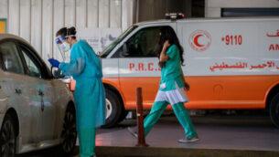 أحد أفراد الطاقم الطبي في مركز شعاري تسيديك الطبي في القدس يرتدي ملابس واقية يأخذ مسحة لاختبار كوفيد-19، 8 أكتوبر، 2020. (Nati Shohat / Flash90)