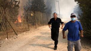 رجلان يفران من حريق في بات حيفر، 9 أكتوبر، 2020. (Gili Yaari / Flash90)