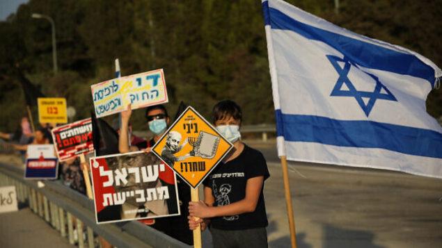 ناشطون يتظاهرون ضد رئيس الوزراء بنيامين نتنياهو على الطريق رقم 3، وسط إسرائيل، 10 أكتوبر 2020 (Nati Shohat / Flash90)