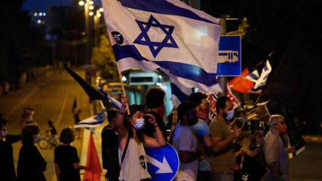 ناشطون يتظاهرون ضد رئيس الوزراء بنيامين نتنياهو في حي بيت هكيرم في القدس، 10 أكتوبر 2020 (Olivier Fitoussi / Flash90)