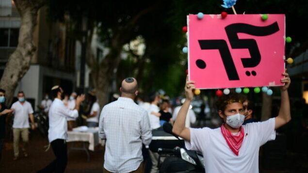 رجل يحتج على رئيس الوزراء بنيامين نتنياهو خلال احتفالات 'سيمحات توراة' في تل أبيب، 10 أكتوبر 2020 (Tomer Neuberg / Flash90)