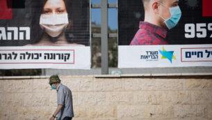 اشخاص يمرون بجانب لوحة اعلانية نشرتها وزارة الصحة تطلب من الناس ارتداء الكمامات، في القدس، 11 أكتوبر، 2020. (Yonatan Sindel / Flash90)
