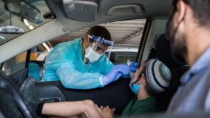 عامل طبي يأخذ مسحة لفحص فيروس كورونا في مستشفى شعاري تسيديك في القدس، 12 أكتوبر 2020 (Nati Shohat / Flash90)