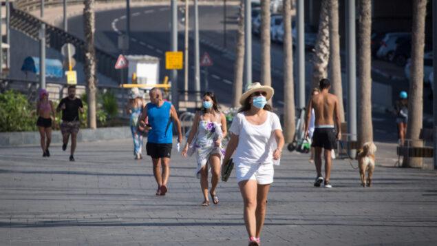 أشخاص على الشاطئ في تل أبيب خلال إغلاق وطني، 15 أكتوبر 2020 (Miriam Alster / FLASH90)