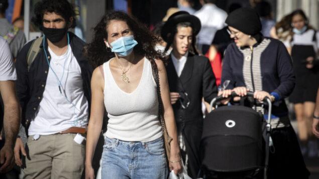 أشخاص يرتدون أقنعة يسيرون في وسط مدينة القدس، خلال إغلاق على مستوى البلاد، 15 أكتوبر 2020 (Olivier Fitoussi / Flash90)