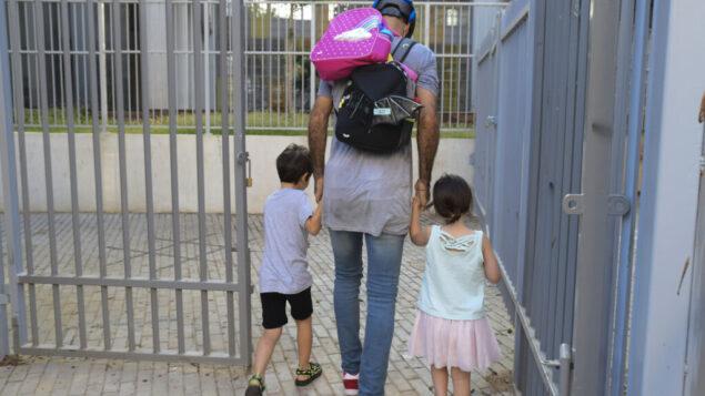 أولياء الأمور يرافقون أطفالهم إلى روضة الأطفال في تل أبيب عند عودتهم بعد تخفيف الإغلاق الوطني، 18 أكتوبر 2020 (Avshalom Sassoni / Flash90)