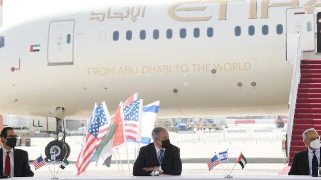 من اليسار إلى اليمين: الوزير الأمريكي منوشين، ورئيس الوزراء نتنياهو، ووزير الدولة الإماراتي للشؤون المالية عبيد حميد الطاير، في حفل وقعت خلاله إسرائيل والإمارات على أربع اتفاقيات ثنائية في مطار بن غوريون في تل أبيب، 20 أكتوبر، 2020. (Amos Ben Gershom/GPO)