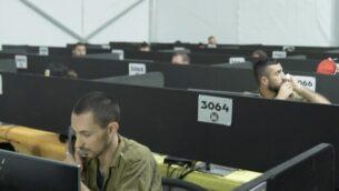 توضيحية: في مقطع فيديو نشره الجيش الإسرائيلي في 29 يوليو، 2020، يظهر جندي إسرائيلى على الهاتف في مقر قيادة الجبهة الداخلية للجيش الإسرائيلي خلال زيارة قام بها منسق كورونا الوطني البروفيسور روني غامزو. (Screen capture: Israel Defense Forces)