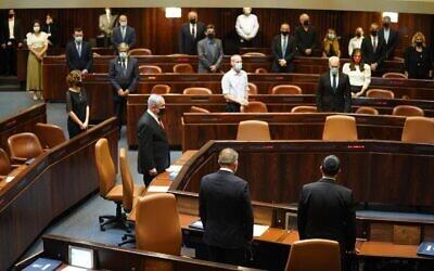 أعضاء الكنيست يقفون دقيقة صمت خلال جلسة مكتملة النصاب لإحياء ذكرى مرور 25 عاما على اغتيال رئيس الوزراء يتسحاق رابين، 29 أكتوبر 2020 (Shmulik Grossman / Knesset)