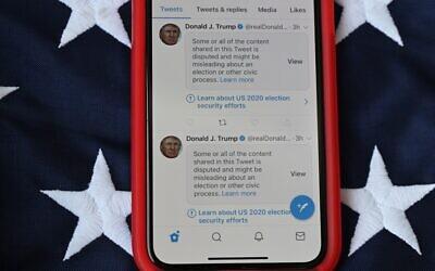 تُظهر هذه الصورة التوضيحية هاتفا محمولا موضوعا على علم الولايات المتحدة مع تغريدات من الرئيس الأمريكي دونالد ترامب وضعت عليها تويتر تحذيرات تفيد بأنها قد تكون غير صحيحة، 5 نوفمبر 2020 مع استمرار فرز الأصوات في تحديد الفائز في الانتخابات الرئاسية.(P Robyn Beck / AFP)