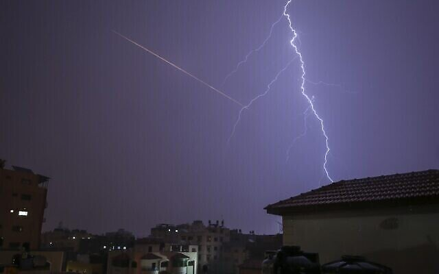 تظهر هذه الصورة المأخوذة من مدينة غزة وميض برق فوق المباني حيث تظهر وهج صاروخ تم إطلاقه في مكان قريب خلال عاصفة رعدية في مدينة غزة، 15 نوفمبر، 2020. (MOHAMMED ABED / AFP)
