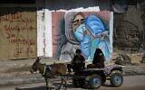 رجل فلسطيني وزوجته يركبان عربة يجرها حمار أمام فن الشارع يمران من أمام رسم على الحائط لطبيبين يرتديان الكمامة بسبب جائحة كوفيد -19 في مخيم النصيرات وسط قطاع غزة، 16 نوفمبر، 2020. (MOHAMMED ABED / AFP)