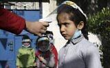 فحص درجة حرارة أطفال فلسطينيين يرتدون دروع واقية بسبب جائحة كوفيد-19 عند وصولهم إلى روضة أطفال في مدينة غزة، 23 نوفمبر، 2020. (MOHAMMED ABED / AFP)