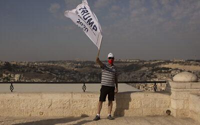 أحد أنصار الرئيس الأمريكي دونالد ترامب يلوح بعلم حملته في تجمع ينادي إلى إعادة انتخابه، في متنزه يطل على مدينة القدس، 27 أكتوبر 2020. (AP / Maya Alleruzzo)