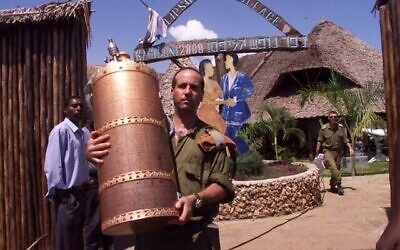 جندي إسرائيلي يزيل لفافة توراة من فندق بارادايس المملوك لإسرائيليين يوم الجمعة، 29 نوفمبر 2002، في كيكامبالا ، بالقرب من مدينة مومباسا الكينية. الانفجار  الانفجار في فندق بارادايس أسفر عن عن مقتل 10 كينيين وثلاثة إسرائيليين وثلاثة انتحاريين. (AP Photo / Karel Prinsloo)