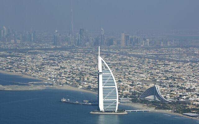 برج العرب، فندق فخم، في المقدمة، وبرج دبي، أطول مبنى في العالم، في خلفية الصورة في المركز، كما يظهران من طائرة في دبي، الإمارات العربية المتحدة، 3 يناير، 2010. (AP Photo / Kamran Jebreili)