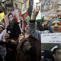"""أقارب أسرى فلسطينيين في السجون الإسرائيلية يحملون صورا لهم خلال تظاهرة لإحياء """"يوم الأسير"""" في مدينة رام الله بالضفة الغربية،  7 أبريل، 2019. (AP Photo/Majdi Mohammed)"""