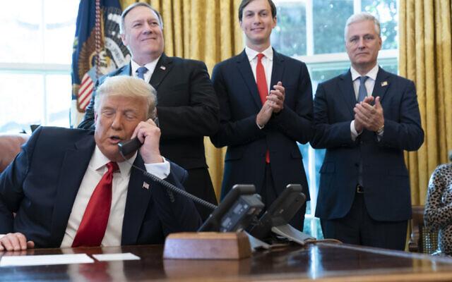 الرئيس الأمريكي دونالد ترامب يتحدث في مكالمة هاتفية مع قادة السودان وإسرائيل، بينما يصفق وزير الخارجية مايك بومبيو، يسار، مستشار البيت الأبيض جاريد كوشنر، ومستشار الأمن القومي روبرت أوبراين، في المكتب البيضاوي للبيت الأبيض، 23 أكتوبر 2020 (AP Photo/Alex Brandon)