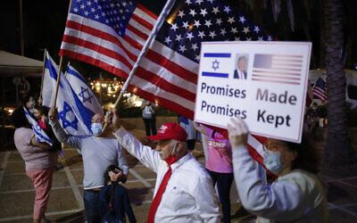 أنصار الرئيس الأمريكي دونالد ترامب يلوحون بالأعلام  الإسرائيلية والأمريكية يوم الانتخابات الرئاسية الأمريكية، في كرميئيل، شمال إسرائيل، 3 نوفمبر، 2020. (AP Photo / Ariel Schalit)