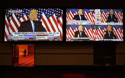 بث مباشر للرئيس دونالد ترامب وهو يتحدث من البيت الأبيض على الشاشات في ليلة الانتخابات، 3 نوفمبر 2020، في لاس فيغاس. (AP/John Locher)