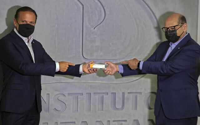 حاكم ساو باولو جواو دوريا، يسار، ومدير معهد بوتانتان ديماس كوفاس يحملان صندوقًا من لقاح تجريبي لكوفيد-19 يتم اختباره بالشراكة مع شركة الأدوية الصينية Sinovac خلال مؤتمر صحفي في ساو باولو، البرازيل، 9 نوفمبر 2020 (AP Photo / Andre Penner)