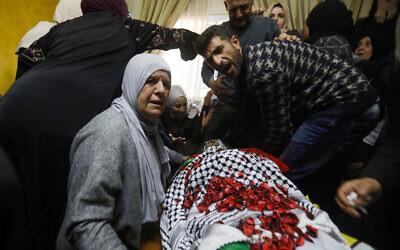 أقارب أحمد جمال مناصرة (26 عاما) حول جثمانه خلال مراسم تشييعه في قرية وادي فوقين بالضفة الغربية بالقرب من بيت لحم، 21 مارس 2019 (Wisam Hashlamoun/Flash90)