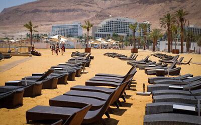 كراسي تشمس خالية على شاطئ بالقرب من مجمع فندق البحر الميت، 10 يوليو، 2019. (Gershon Elinson / Flash90)
