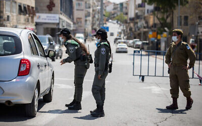 توضيحية: عناصر من شرطة حرس الحدود وجندي من الجيش الإسرائيلي عند حاجز مؤقت في القدس، 14 أبريل، 2020، قبل بدء الإغلاق على مستوى البلاد بمناسبة عيد الفصح العبري. (Nati Shohat / Flash90)