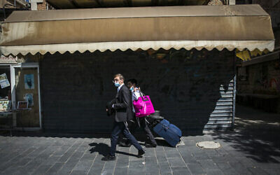 إسرائيليون يمرون أمام متجر مغلق خارج سوق محانيه يهودا في القد ، 23 سبتمبر، 2020، خلال إغلاق عام لمنع انتشار كوفيد-19. (Olivier Fitoussi / Flash90)