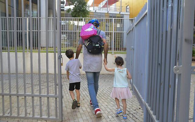 أب يرافق طفليه الى روضة اطفال في تل ابيب، 18 أكتوبر، 2020. (Avshalom Sassoni / Flash90)