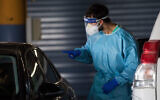 عضو فريق طبي يأخذ مسحة لتشخيص كورونا في مستشفى شعاري تسيديك في القدس، 26 أكتوبر، 2020. (Yonatan Sindel / Flash90)