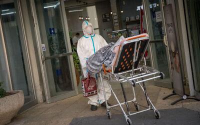 عامل في نجمة داوود الحمراء ينقل مريضا إلى وحدة كورونا في مستشفى هداسا عين كارم في القدس، 1 نوفمبر، 2020. (Yonatan Sindel / Flash90)