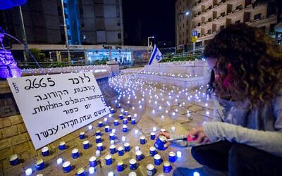 أشخاص يقفون بجانب شموع LED وضعها نشطاء من حركة 'داركينو' تخليدا لذكرى ضحايا فيروس كورونا الإسرائيليين، بالقرب من المقر الرسمي لرئيس الوزراء في القدس، 8 نوفمبر ، 2020. على اللافتة كُتب أن عدد ضحايا كورونا وصل إلى مستوى عدد القتلى في حرب يوم الغفران عام 1973 وهو ما يستدغي تشكيل لجنة تحقيق. (Olivier Fitoussi / Flash90)