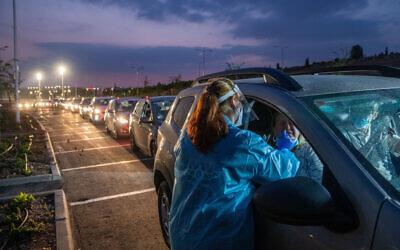 عمال الرعاية الصحية يأخذون عينات في موقع اختبار فيروس كورونا من السيارة في موديعين، 9 نوفمبر 2020 (Yossi Aloni / Flash90)