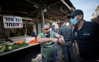 تجار محليون يفتحون أكشاكهم في سوق الكرمل احتجاجا على الإغلاق المستمر للسوق، تل أبيب، 17 نوفمبر، 2020. (Miriam Alster / Flash90)