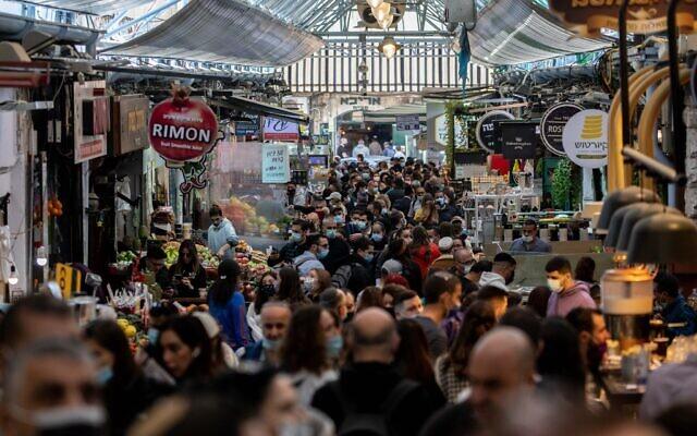 اشخاص يتسوقون في سوق محانيه يهودا في القدس، 27 نوفمبر 2020 (Yonatan Sindel / Flash90)