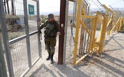توضيحية: صورة تم التقاطها في 8 نوفمبر 2019، يظهر فيها جندي إسرائيلي يغلق بوابة حدودية على الجانب الإسرائيلي من الحدود في موقع نهاريم في غور الأردن.(Menahem Kahana/AFP)