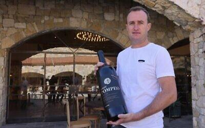 صانع النبيذ الإسرائيلي يعقوب بيرغ يحمل زجاجة نبيذ أحمر  تحمل اسم وزير الخارجية الأمريكي مايك بومبيو في مصنع بساغوت للنبيذ في المنطقة الصناعيةالاستيطانية في شاعر بنيامين بالقرب من مستوطنة بساغوت بالضفة الغربية، شمال القدس، 18 نوفمبر، 2020.  (Emmanuel Dunand / AFP)