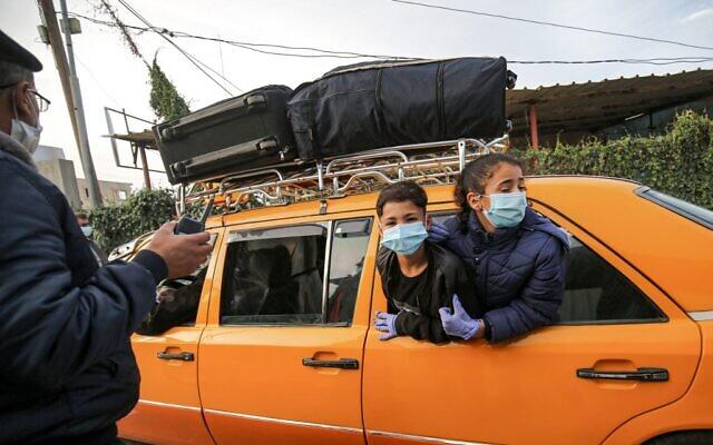 أطفال يرتدون أقنعة بسبب جائحة كوفيد-19، ينظرون من نافذة سيارة تقل فلسطينيين على وشك العبور إلى الجانب المصري عبر معبر رفح الحدودي بين قطاع غزة ومصر، 24 نوفمبر 2020 (SAID KHATIB / AFP)