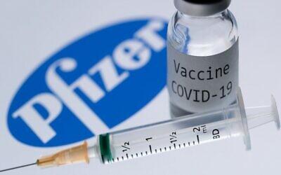 """صورة توضيحية لحقنة وزجاجة مكتوب عليها """"لقاح كوفيد-19"""" بجانب شعار شركة """"فايزر""""، 23 نوفمبر 2020 (JOEL SAGET / AFP)"""