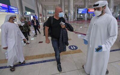 صورة توضيحية: رجل إسرائيلي يسير أمام الطاقم الإماراتي بعد مراقبة جوازات السفر عند وصوله من تل أبيب إلى مطار دبي في الإمارات، 26 نوفمبر 2020 (Karim SAHIB / AFP)