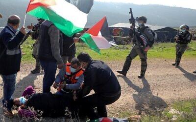 فلسطينيون يساعدون متظاهرا مصابا وسط اشتباكات مع قوات الامن الاسرائيلية في اعقاب مظاهرة ضد توسيع الاستيطان في بلدة سلفيت في الضفة الغربية، 4 ديسمبر 2020 (JAAFAR ASHTIYEH / AFP)
